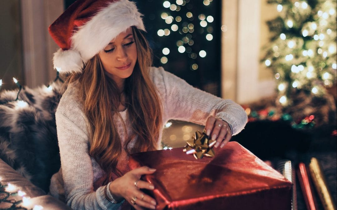 Woman as Santa putting bow on present
